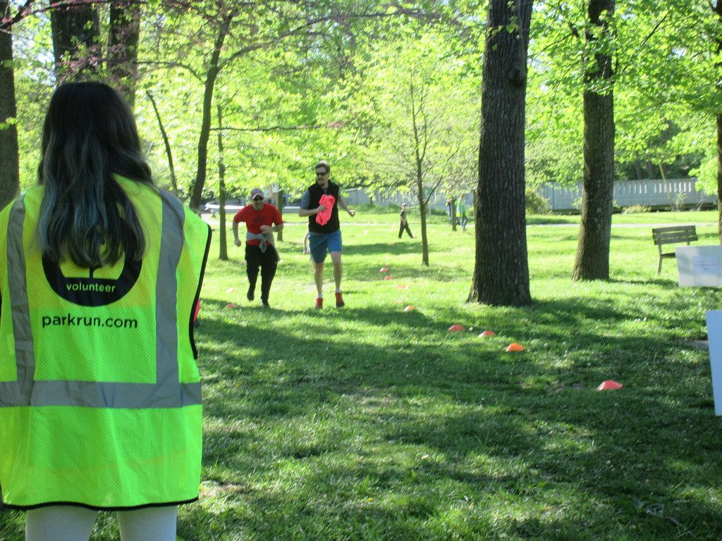 The back of a female parkrun volunteer in hi-vis stoo in a park with two runners running towards her