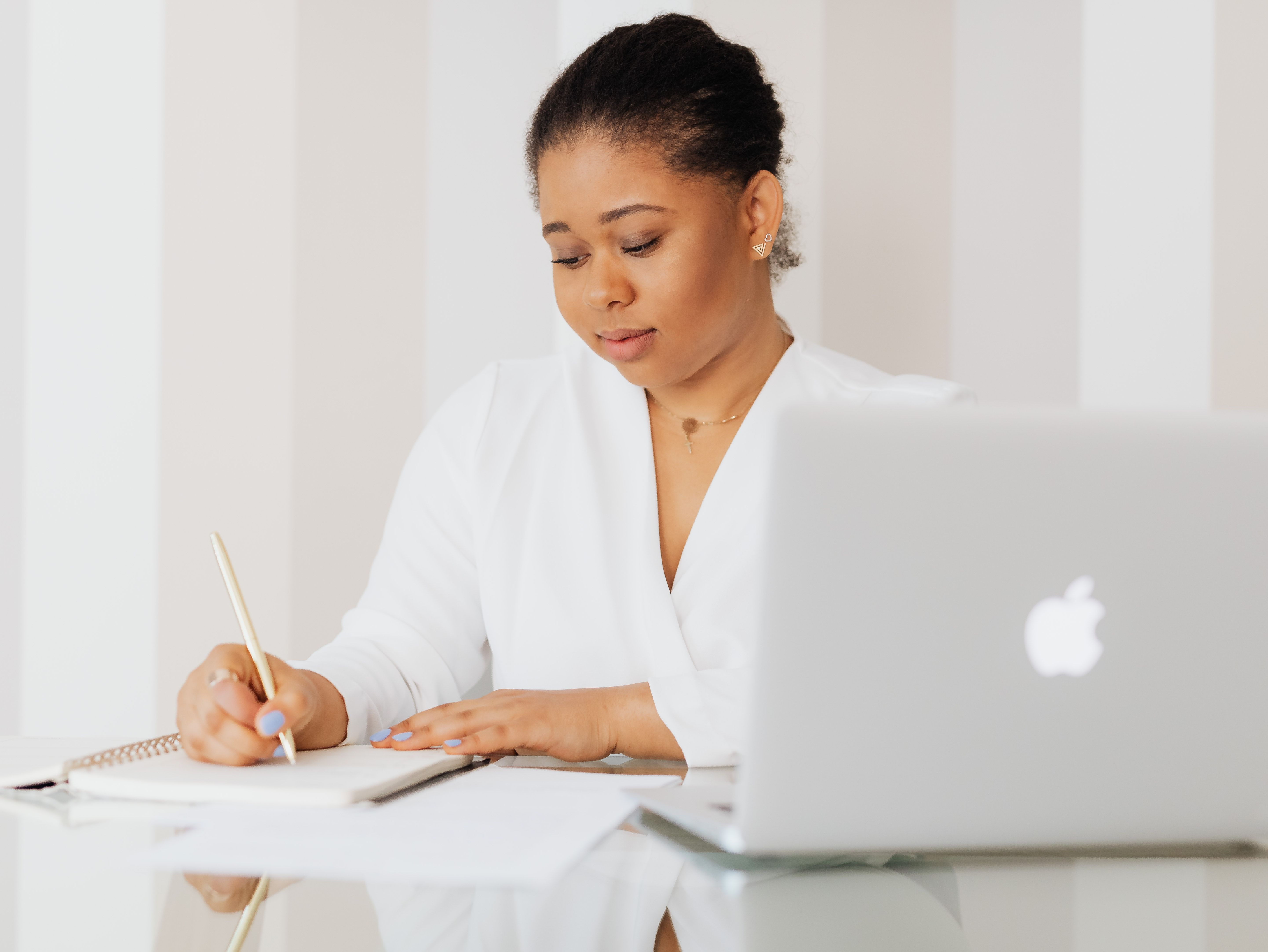 A woman writing in a note book next to her open laptop