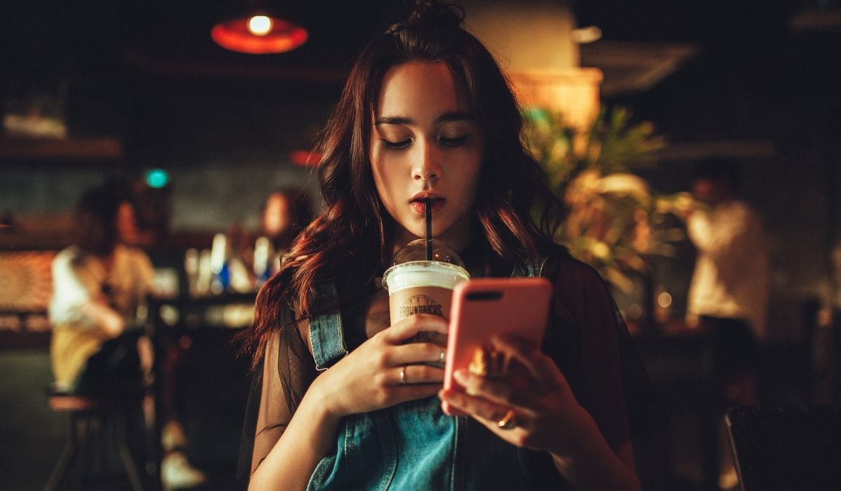 Girl looking at an iPhone and drinking an iced coffee