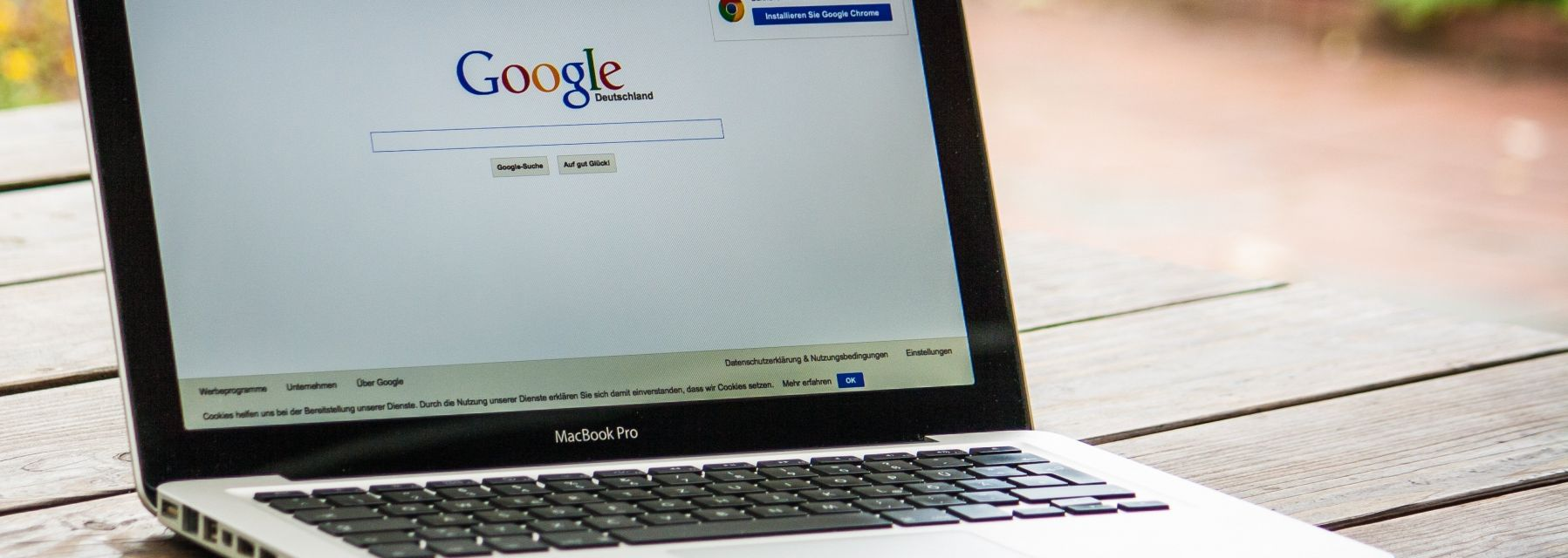 A macbook on a table showing google
