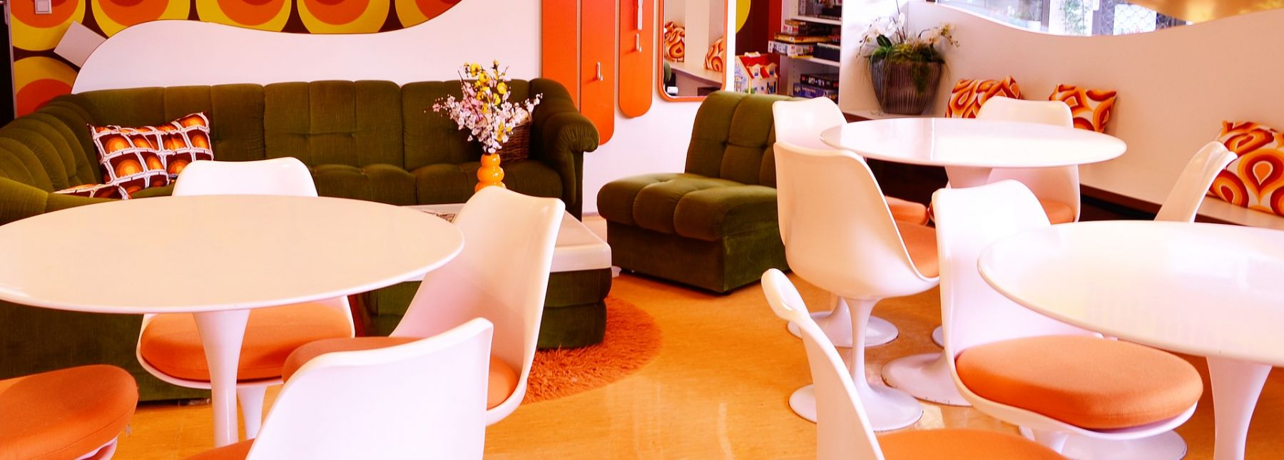 A room with tulip chairs and tables