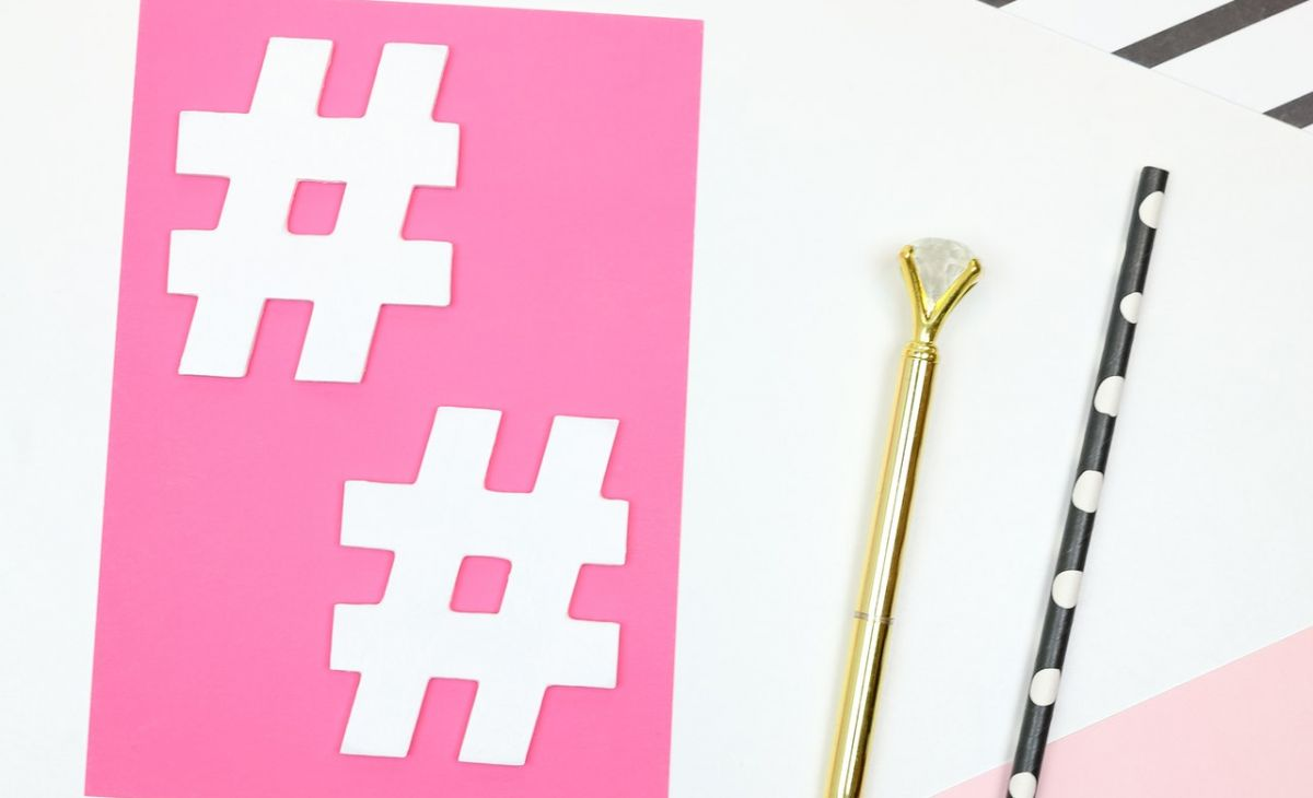 A desk with paper cutouts of hashtag symbols in white laying over pink paper