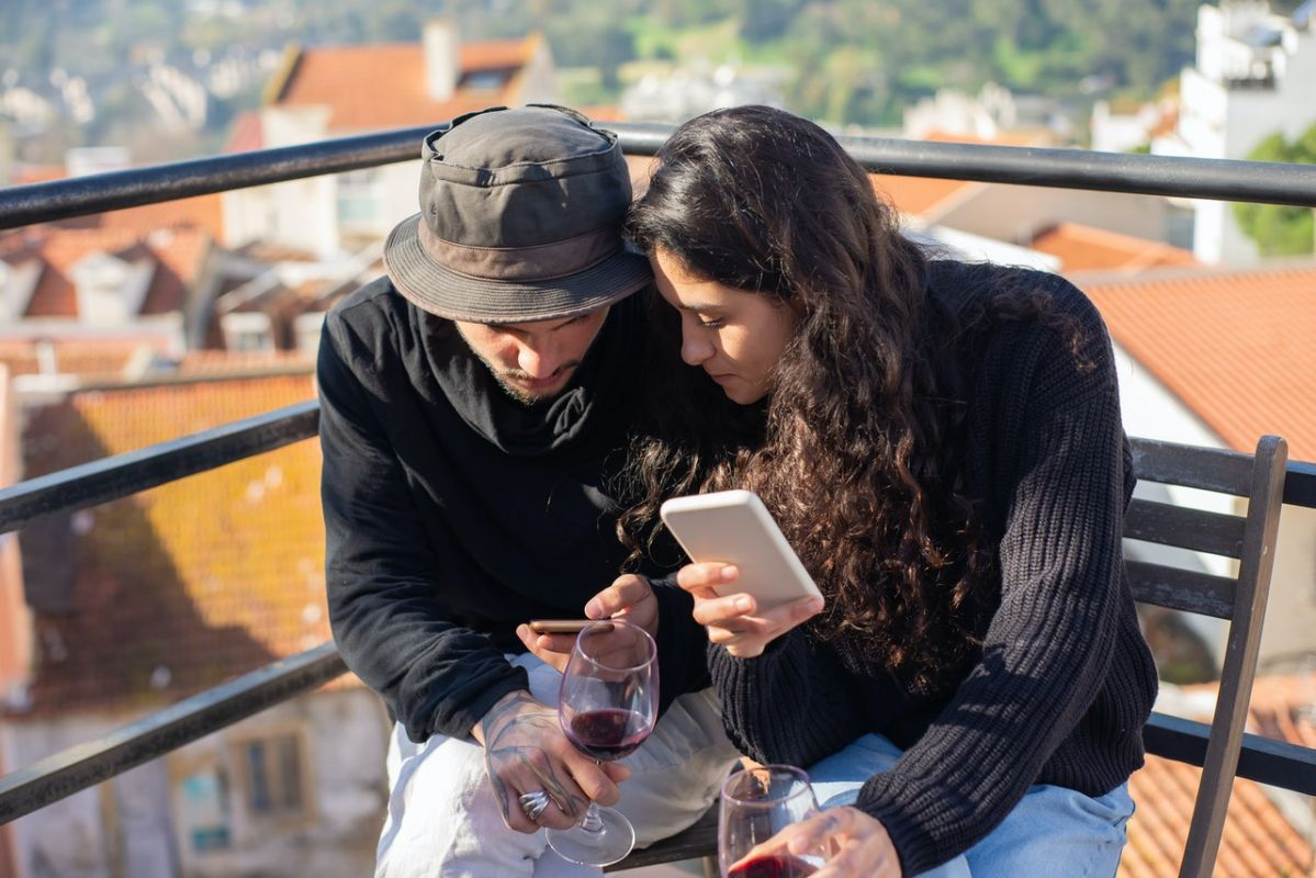 A couple drinking wine and looking at each others smart phones